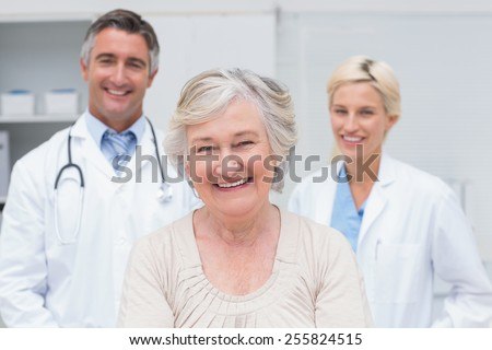Portrait of senior patient smiling with doctors in clinic - stock photo