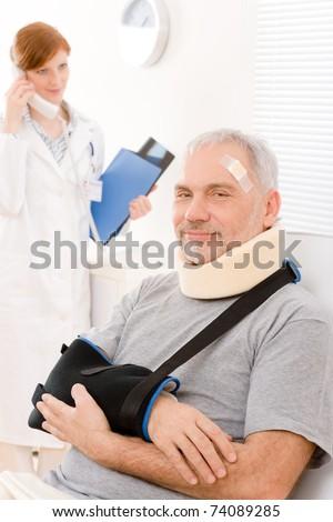 Portrait of senior patient with broken arm in doctor office - stock photo