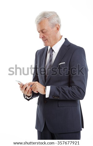 Portrait of senior professional businessman using his mobile phone and texting while standing at isolated white background.