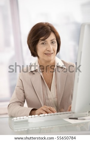 Portrait of senior professional woman sitting at desk, using computer, looking at camera. - stock photo