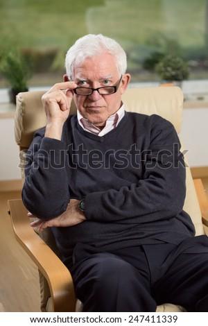 Portrait of senior psychotherapist sitting on armchair - stock photo