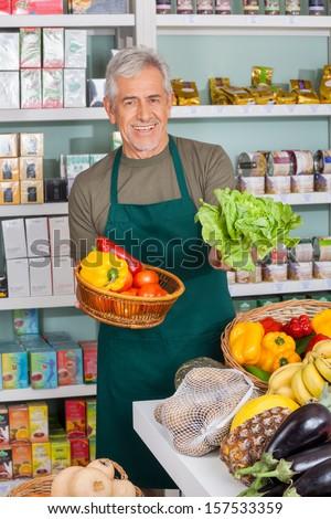 Portrait of senior salesman selling vegetables in supermarket - stock photo