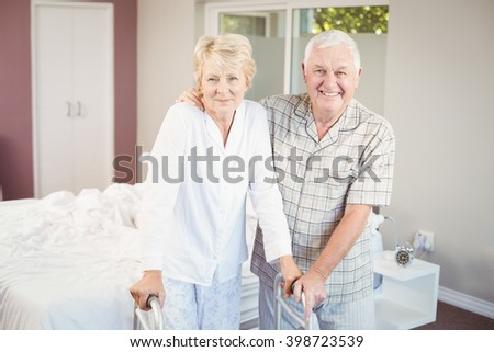 Portrait of senior smiling couple with walker at home - stock photo