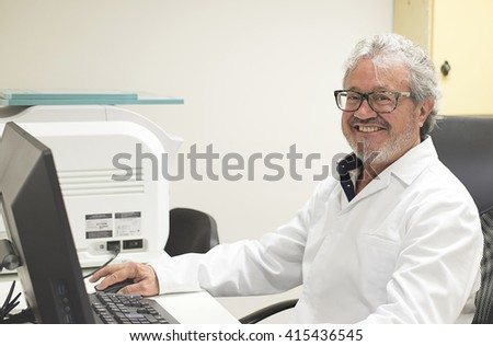 Portrait of senior smiling doctor working at computer