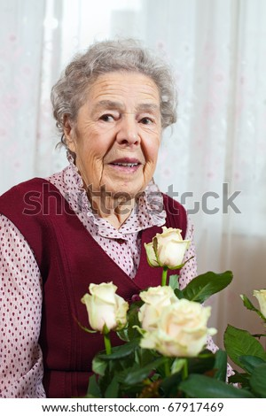 Portrait of senior smiling woman with bunch of roses - stock photo