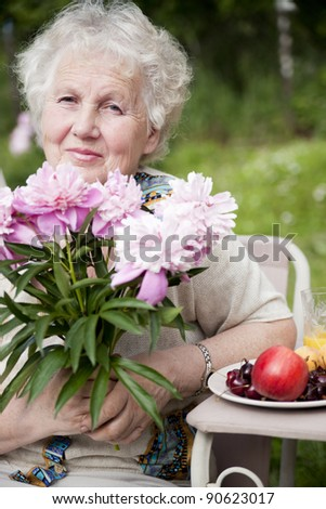 Portrait of senior smiling woman with flowers and fruit - stock photo