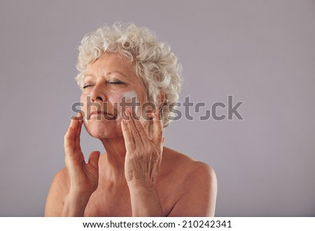 Portrait of senior woman applying lotion on her face against grey background. Mature caucasian woman applying anti-wrinkle face cream. - stock photo