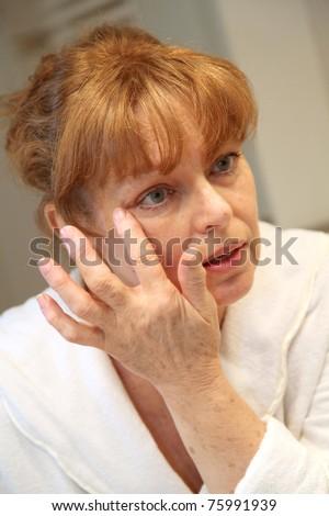 Portrait of senior woman applying moisturizing cream - stock photo