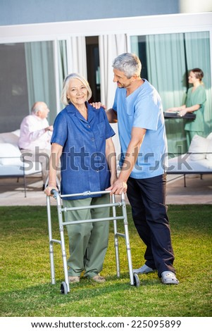Portrait of senior woman being assisted by male caretaker in using Zimmer frame at nursing home lawn - stock photo