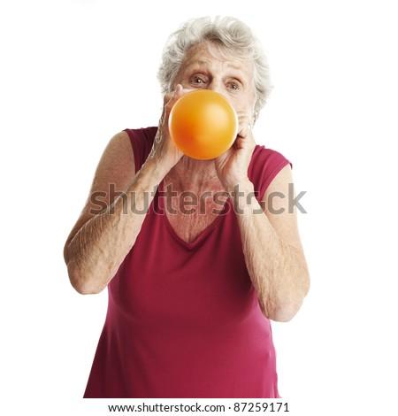 portrait of senior woman blowing a balloon - stock photo