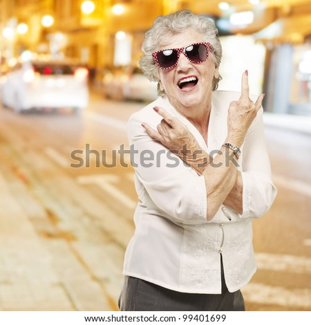 portrait of senior woman doing rock symbol against a city night - stock photo