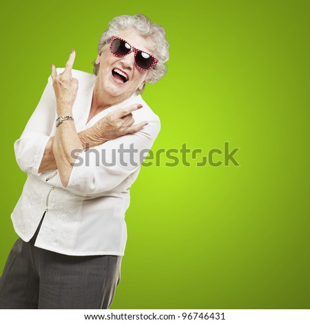 portrait of senior woman doing rock symbol over green background - stock photo