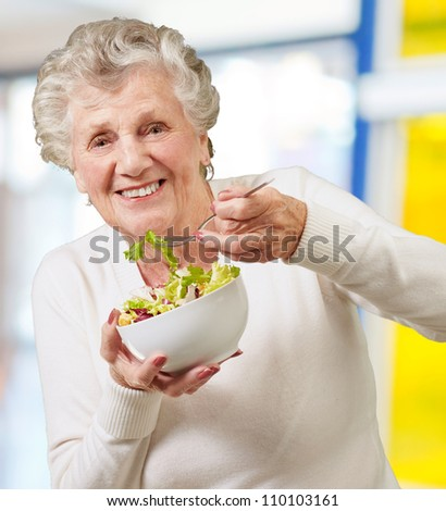 portrait of senior woman eating a fresh salad indoor - stock photo