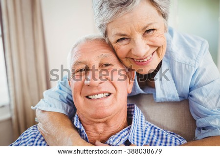 Portrait of senior woman embracing man in living room - stock photo