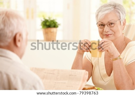Portrait of senior woman having morning coffee, smiling at camera, sitting in kitchen with husband.? - stock photo
