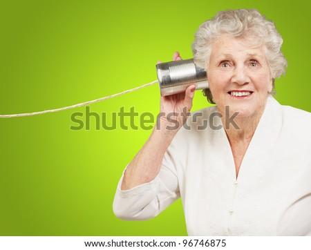 portrait of senior woman hearing with metal tin can over green background - stock photo