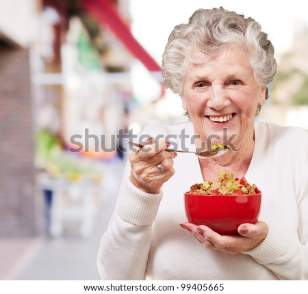 portrait of senior woman holding a cereals bowl against a vegetable shop - stock photo