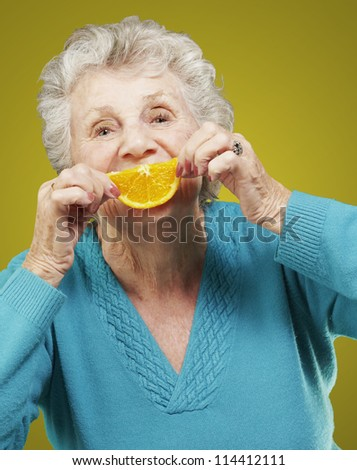portrait of senior woman holding a orange slice in front of her mouth over yellow background - stock photo