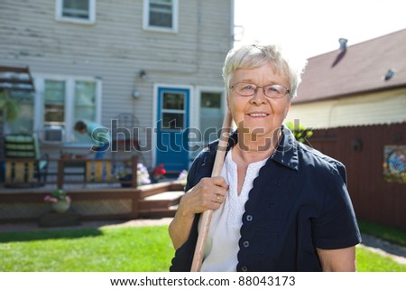 Portrait of senior woman holding gardening tool with friend in the background - stock photo