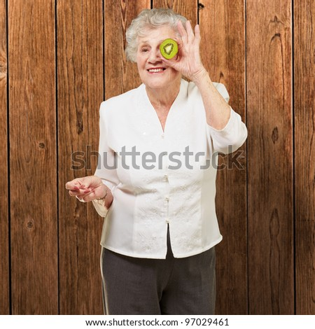 portrait of senior woman holding kiwi in front of her eye against a wooden wall - stock photo