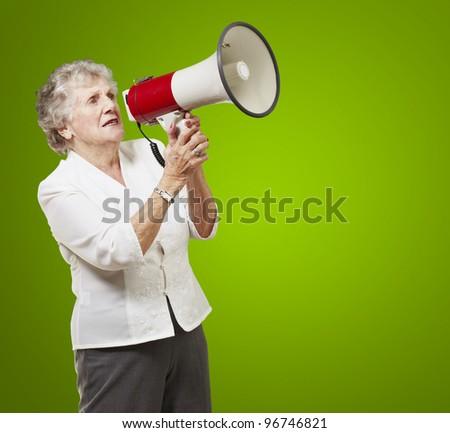 portrait of senior woman holding megaphone over green background - stock photo