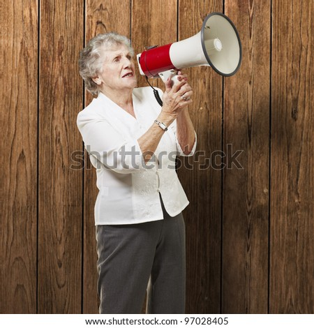 portrait of senior woman holding megaphone over wooden wall - stock photo