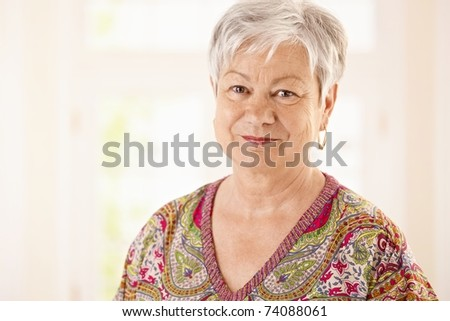 Portrait of senior woman in colorful shirt, looking at camera, smiling.? - stock photo