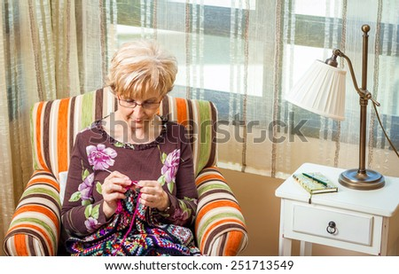 Portrait of senior woman knitting a vintage wool quilt with colorful patches - stock photo