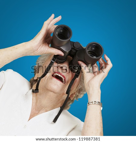 portrait of senior woman looking through a binoculars against a blue background - stock photo