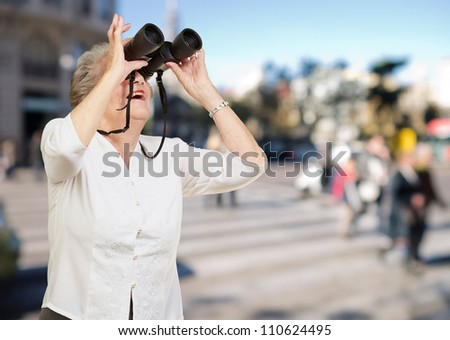portrait of senior woman looking through a binoculars at crowded street - stock photo