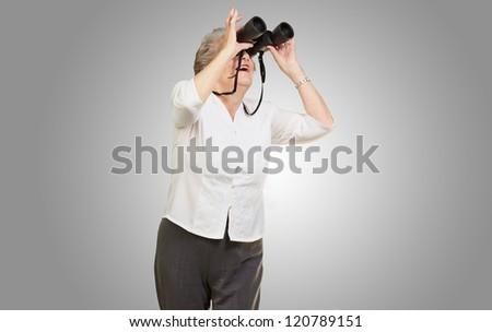 portrait of senior woman looking through a binoculars over grey background - stock photo