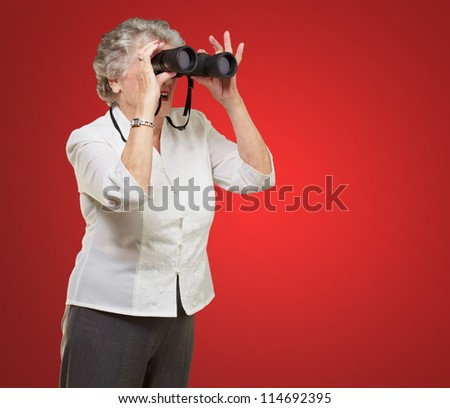 portrait of senior woman looking through a binoculars over red background - stock photo