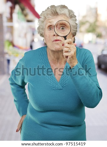 portrait of senior woman looking through a magnifying glass against a city - stock photo