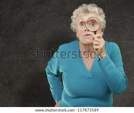 portrait of senior woman looking through a magnifying glass against a grunge wall - stock photo