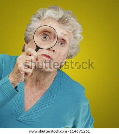 portrait of senior woman looking through a magnifying glass over yellow background - stock photo