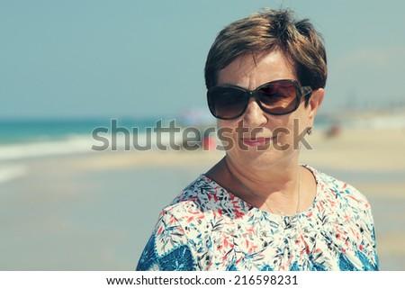 Portrait of senior woman on summer vacation at sea - stock photo