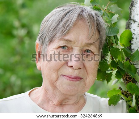 Portrait of senior woman outdoors in a summer - stock photo