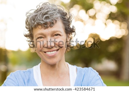 Portrait of senior woman relaxing at park. Close up face of happy senior woman looking at camera. Portrait of a smiling mature woman with grey hair. - stock photo