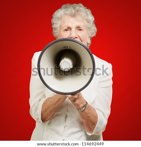 portrait of senior woman screaming with megaphone over red background - stock photo