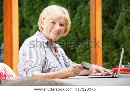 Portrait of senior woman shopping online. Happy female holding credit card in her hand while sitting at home in the garden and using laptop.  - stock photo