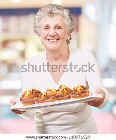portrait of senior woman showing a chocolate muffin tray indoor - stock photo