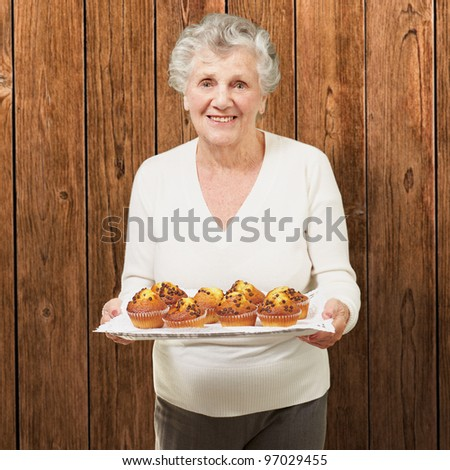 portrait of senior woman showing homemade muffins against a wooden wall - stock photo