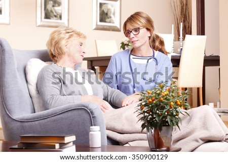 Portrait of senior woman sitting at home in living room while caregiver giving helping hand.  - stock photo
