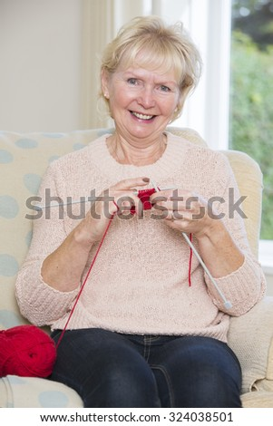 Portrait Of Senior Woman Sitting In Chair Knitting - stock photo