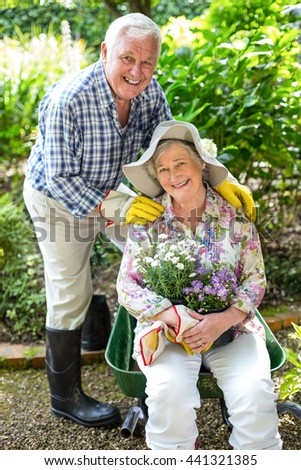 Portrait of senior woman sitting in wheelbarrow by husband in garden