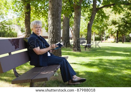 Portrait of senior woman sitting on a park bench reading a book - stock photo