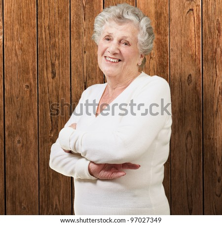 portrait of senior woman smiling against a wooden wall - stock photo