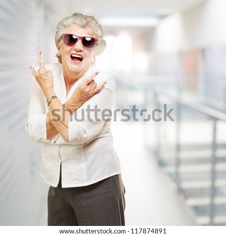 portrait of senior woman smiling and wearing sunglasses at modern office - stock photo