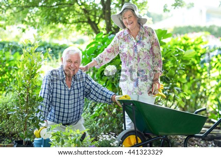 Portrait of senior woman standing by husband with wheelbarrow in garden - stock photo