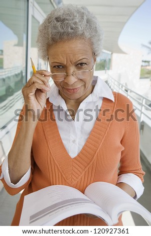 Portrait of senior woman standing with book - stock photo